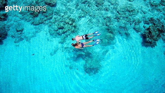 Aerial view of couple snorkeling in turquoise water - gettyimageskorea