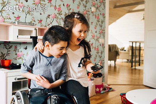 Cheerful sister watching video with autistic brother on smart phone at home - gettyimageskorea