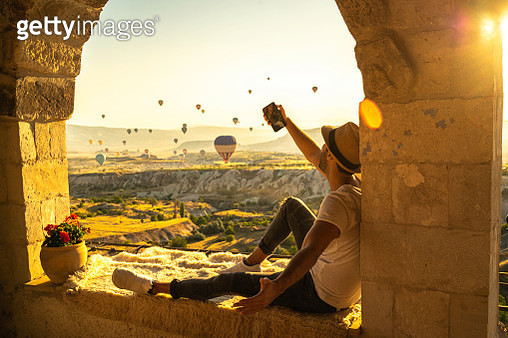 Side View Of A Young Man Taking A Selfie Sitting And Looking At View During Ballooning Festival - gettyimageskorea