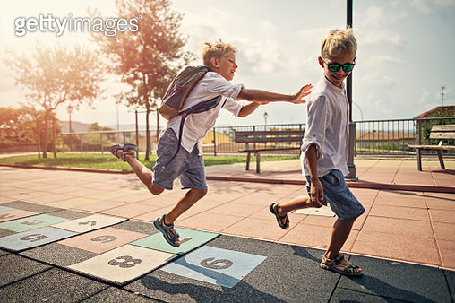 Little boys playing in schoolyard. One boy is pushing another and both are laughing. Nikon D850 - gettyimageskorea