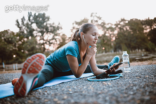 Young Cute Female Preparing Playlist for Outdoor Aerobics Pilates Training - gettyimageskorea