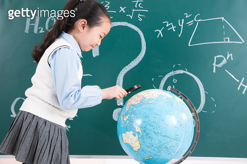 Elementary school students use a magnifying glass globe - gettyimageskorea