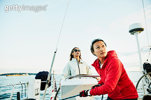 Female sailor trimming sail during race on summer evening - gettyimageskorea
