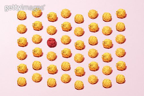 Standing Out from the Crowd Concept of a Red Colored Crumpled Paper Ball among Yellow Paper Balls on Pink Background. - gettyimageskorea