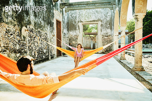 Laughing woman in discussion with boyfriend while relaxing in hammocks at luxury resort - gettyimageskorea