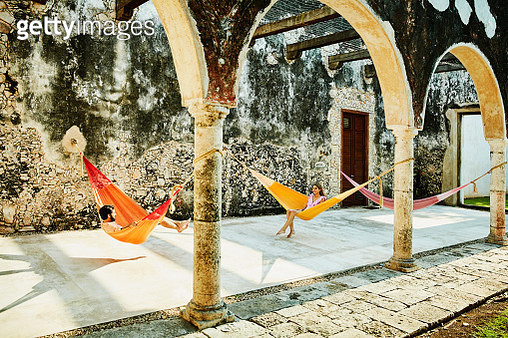 Couple relaxing in hammocks at luxury resort - gettyimageskorea