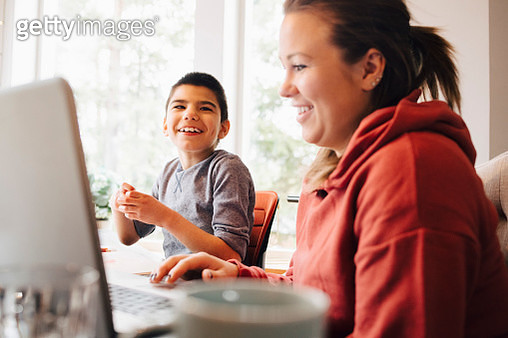 Mother using laptop while sitting with happy autistic son in living room at home - gettyimageskorea