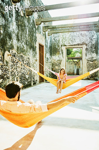 Smiling woman looking at boyfriend while relaxing in hammock at luxury resort - gettyimageskorea