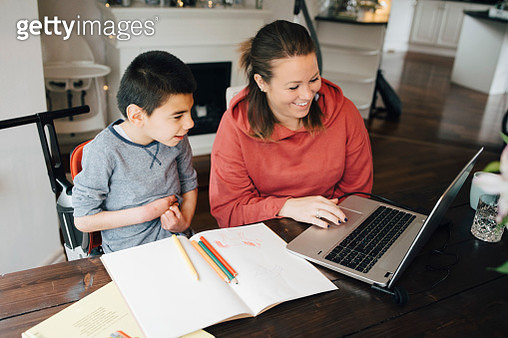 Smiling mother showing video to autistic son on laptop at home - gettyimageskorea