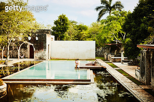 Embracing couple standing at edge of pool in courtyard of luxury tropical resort - gettyimageskorea