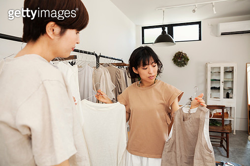 Two Japanese women standing in a small fashion boutique, looking at tops. - gettyimageskorea