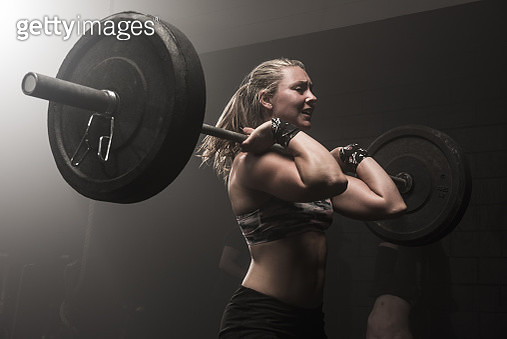 Young woman lifting barbell - gettyimageskorea