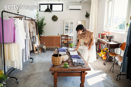Japanese woman standing in a small fashion boutique, looking at T-Shirts on a coffee table. - gettyimageskorea