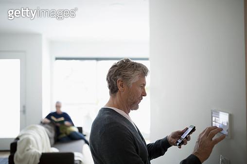 Senior man using smart phone app, adjusting digital thermostat - gettyimageskorea