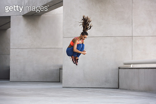 Side view of young woman jumping hugging knees in mid air - gettyimageskorea