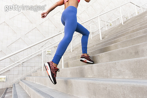 Low angle rear view of young woman, wearing sports clothing running up stairs - gettyimageskorea