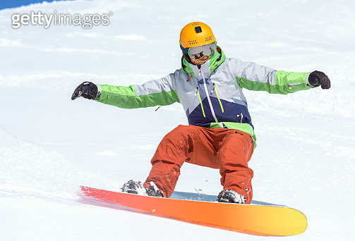 Male snowboarder moving down the slope in a winter landscape - gettyimageskorea
