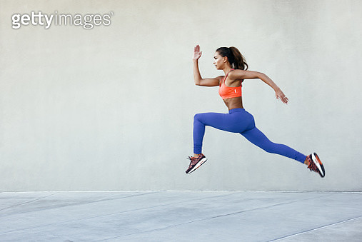 Side view of young woman wearing sports clothing in mid air striding stance - gettyimageskorea