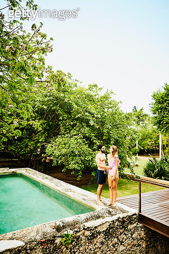 Laughing couple standing on edge of plunge pool at luxury tropical resort - gettyimageskorea