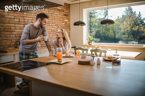 Happy couple in love talking while enjoying in their morning at the kitchen. - gettyimageskorea
