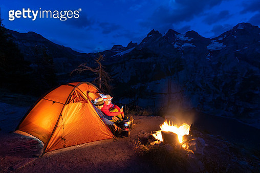 Two hikers in a tent relaxing beside campfire at night, Oeschinensee, Bernese Oberland, Kandersteg, Canton of Bern, Switzerland - gettyimageskorea