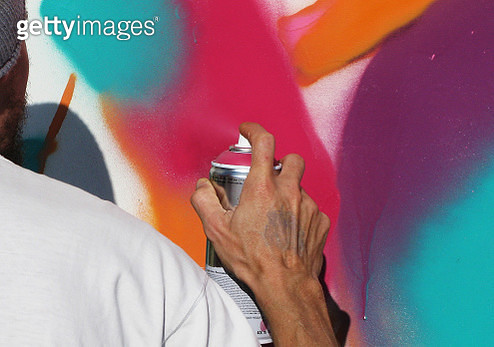Cropped Image Of Man Spray Painting On Wall - gettyimageskorea