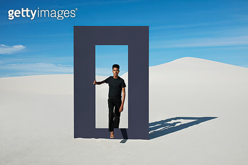 Portrait of young man walking through door frame at desert against sky during sunny day - gettyimageskorea