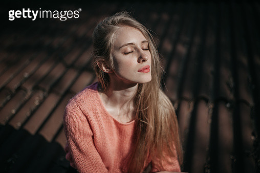 Portrait of young Caucasian woman sitting on the roof at sunrise - gettyimageskorea