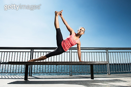 Woman practicing yoga on park bench - gettyimageskorea
