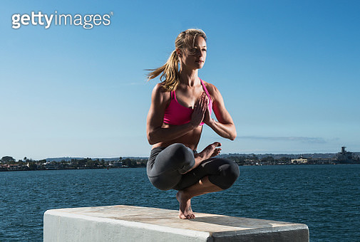 Woman practicing yoga on concrete block - gettyimageskorea