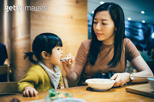 Caring young Asian mother feeding food to cute little daughter while having meal in restaurant - gettyimageskorea