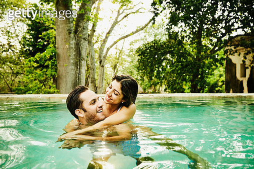 Laughing couple embracing while relaxing in plunge pool at luxury resort - gettyimageskorea