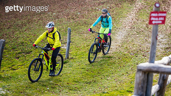 Two female mountain bikers riding on a grassy trail - gettyimageskorea