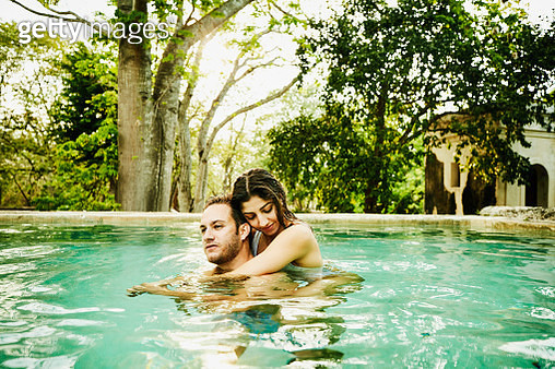 Couple embracing while relaxing in plunge pool at luxury resort - gettyimageskorea