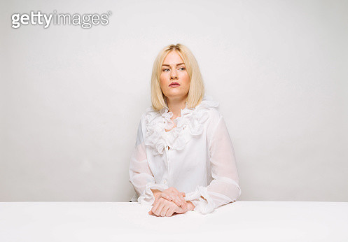 Beautiful blond woman sitting at white table - gettyimageskorea