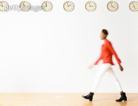 Mixed race businesswoman walking under clocks - gettyimageskorea