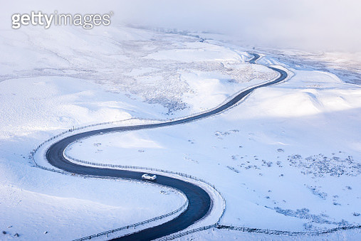 Small car on the bendy road below Mam Tor in the Peak District national park, Derbyshire, England. A beautiful snowy morning in the landscape above the Edale Valley. - gettyimageskorea