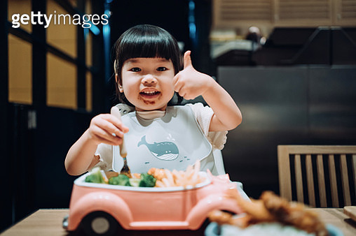 Cute little Asian girl enjoying her kids meal set, feeding herself with a fork while gesturing thumbs up in a restaurant - gettyimageskorea