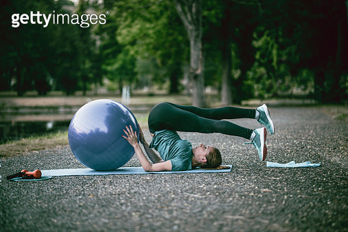 Athletic Female Stretching With Fitness Ball In Park - gettyimageskorea