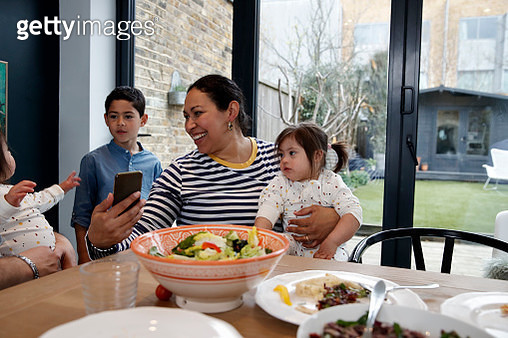 Latin American mother smiling and showing smart phone to children, mobile app, social media - gettyimageskorea