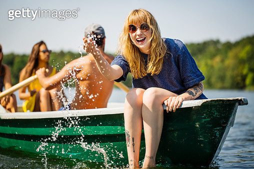 Cheerful young woman splashing water while boating with friends in a lake. Woman enjoying boat ride with man rowing at the back. - gettyimageskorea
