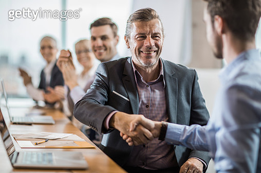 Happy mid adult businessman shaking hands with his colleague on a meeting in the office. - gettyimageskorea