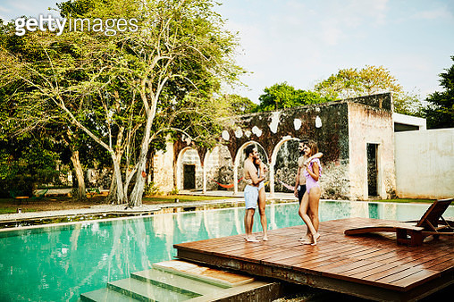 Smiling couples hanging out together at edge of pool at luxury tropical resort - gettyimageskorea