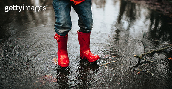 Small child, wearing bright red wellies and jumping in a huge puddle. - gettyimageskorea