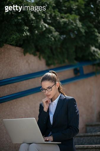 Beautiful young woman using laptop outdoors - gettyimageskorea