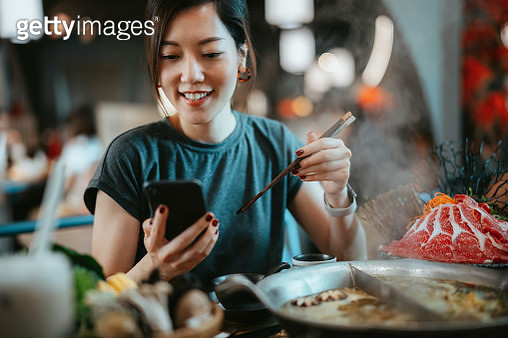 Beautiful smiling young Asian woman using smartphone while enjoying delicious traditional Chinese hotpot with assorted fresh ingredients in restaurant. Chinese cuisine and food. Eating out lifestyle. Technology in everyday life - gettyimageskorea
