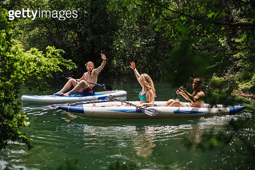 Couple of friends having fun at a lake kayaking and paddleboarding. - gettyimageskorea