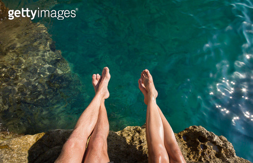 Couple's Legs Above Turquoise Ocean - gettyimageskorea