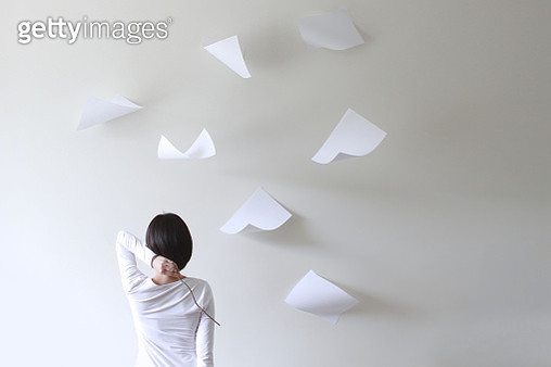 Rear view of a woman holding a stick behind her head with pieces of paper flying around - gettyimageskorea