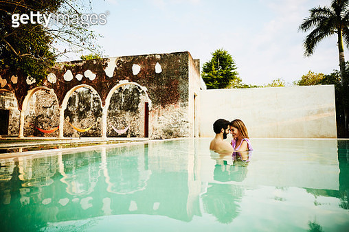 Smiling couple embracing in pool during romantic vacation at luxury tropical resort - gettyimageskorea